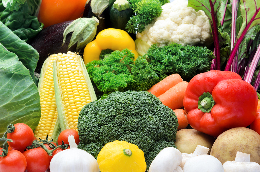 Fresh raw organic vegetable produce, assortment of corn, peppers, broccoli, mushrooms, beets, cabbage, parsley, tomatoes